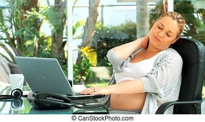 Tired woman working on her laptop at a desk
