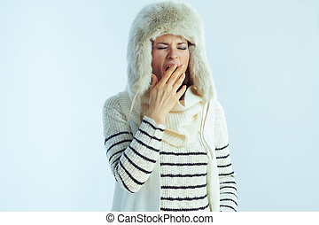 tired woman yawning isolated on winter light blue background