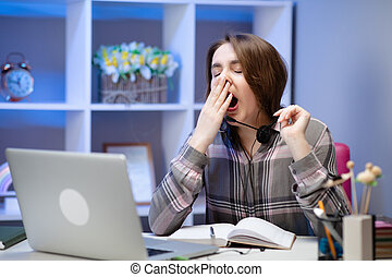 Tired woman yawning, sitting at table with laptop, lazy student doing homework, preparing to pass exam, sleepy girl working on computer after sleepless night, lack of sleep and boredom concept
