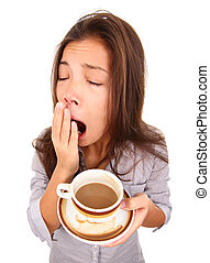 Tired woman yawning spilled a little coffe. Beautiful mixed race asian / caucasian model isolated on white background.