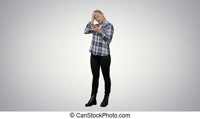 Tired working young woman reading messages on the phone on white background.