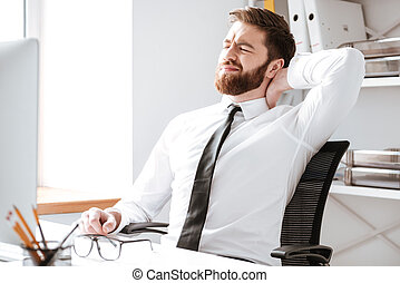 Tired young businessman in office stretching.