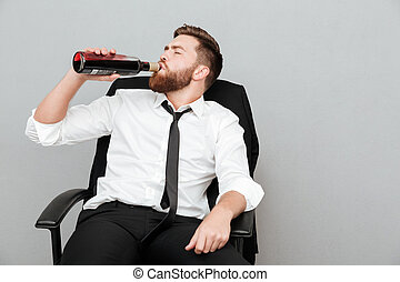 Tired young businessman sitting in office chair