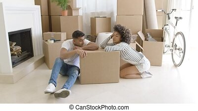 Tired young couple relaxing on cardboard boxes - Tired young...