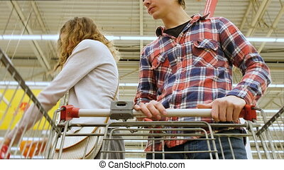 Tired young couple with cart choosing the vegetables at the store, 4K.