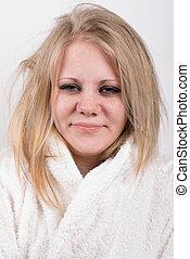 tired young cute woman in bathrobe