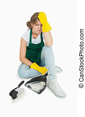 Tired young maid sitting with brush and dust pan over white background