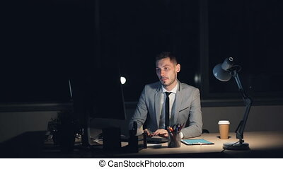 Tired young man in suit is working on computer late at night sitting in office alone finishing job rubbing his face having headache. Overwork and youth concept.