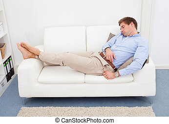 Tired Young Man On Couch - Portrait Of Tired Businessman...