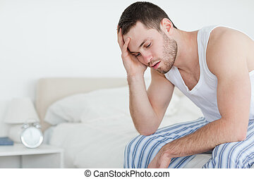 Tired young man sitting on his bed