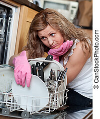 Tired young woman filing the dishwasher in the kitchen