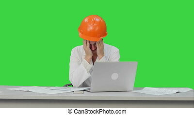 Tired young woman in safety helmet yawning and try to work on a Green Screen, Chroma Key.