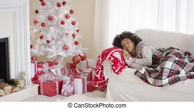 Tired young woman napping in front of an Xmas tree with a...