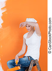 Tired young woman relaxing on ladder while holding paint roller against orange colored wall