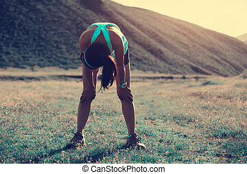 tired young woman runner have a rest on grassland trail