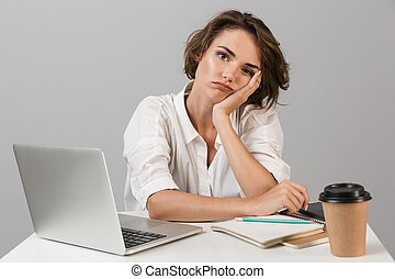 Tired young woman sitting at the table isolated over grey background near laptop computer.