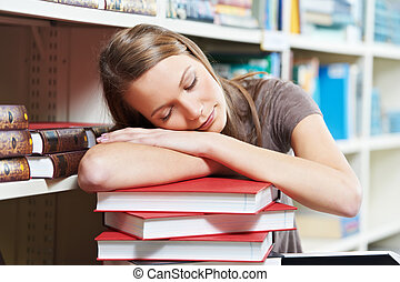 tired young woman sleeping on book in library