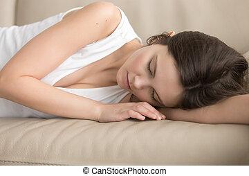Tired young woman sleeping on soft sofa