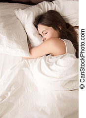 Tired young woman sleeps well in bed