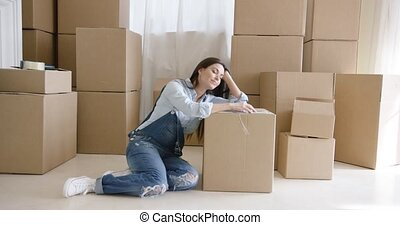 Tired young woman taking a break from packing up her belongings in boxes to renovate her apartment