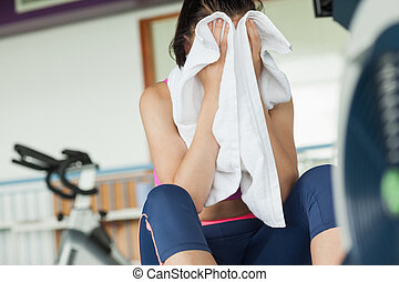 Tired young woman wiping face while working on row machine in fitness studio
