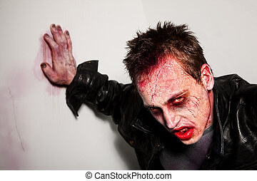 Tired Zombie - Exhausted bloody zombie leaning against a...