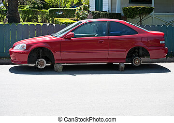 A parked automobile on blocks whose wheels and tires have been stolen