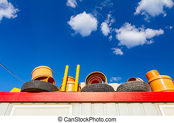 Tires and plastic pipes on the metal roof of the container