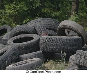 Tires dumped near forest. Environmental pollution.
