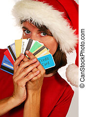 woman in santa hat holding credit cards (holiday debt)