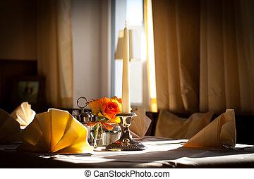 Tischgedeck mit Kerze und Blumen Arranagment