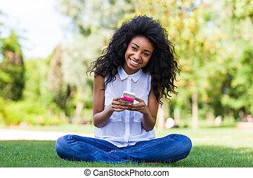 tizenéves, emberek ül, -, fekete, telefon, afrikai, használ, mosolygós, fű, leány