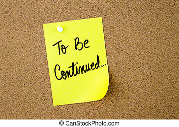 To Be Continued written on yellow paper note pinned on cork board with white thumbtack, copy space available
