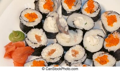 To decorate sushi with red caviar and cheese. - hands,...