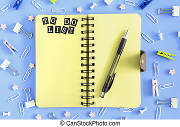 To Do list. Notepad with brown sheets and an inscription . Chaos of stationery. Clips, clothespins and small sprockets scattered on a blue background.