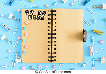To-do list. Open the notepad on springs with brownish pages. Office supplies are scattered in disorder . Pink and blue asterisks.