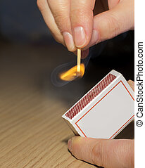To light a match. The woman lights a match fire from a box of matches