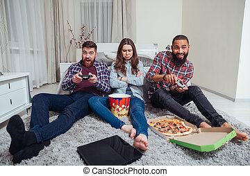 to mænd, spille computer boldspil, og, sørgelige, fornærmede, kvinde sidde