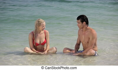 To the beat of waves and ripples - Young couple sitting in...