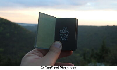 To travel is to live. Book with the inscription. Forest on background..