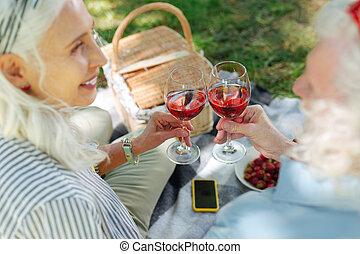 Joyful nice couple cheering with wine