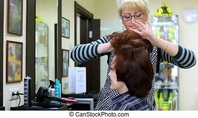 To woman do in hairdressing salon hairdress and comb hair