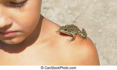 Toad Sitting on the Shoulder of a Young Child on the Beach...