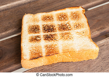 Toast a slice of bread on wooden table