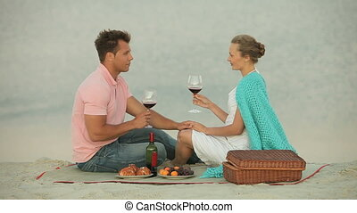 Lovers having picnic at the beach, lovely girl proposing a toast