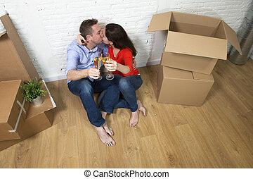 toast, plancher, maison, couple, séance, célébrer, américain, en mouvement, baisers, nouveau, champagne, heureux