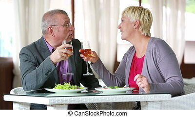 Senior woman making a toast and drinking wine with her husband