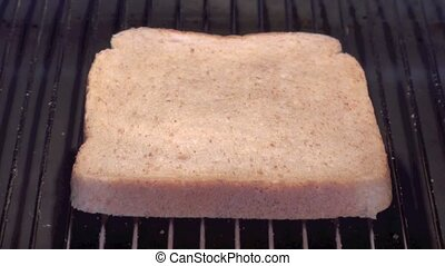 Slice of toast on the grill slowly going brown