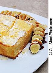 Toast topped with honey and ice-cream , banana