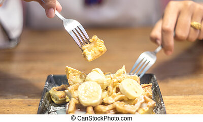 Toast topped with sliced bananas, nuts, egg, cream cheese sauce. Extreme shallow depth of field with selective focus on toast and some blur on corner of plate. Woman / man using a fork to eat.